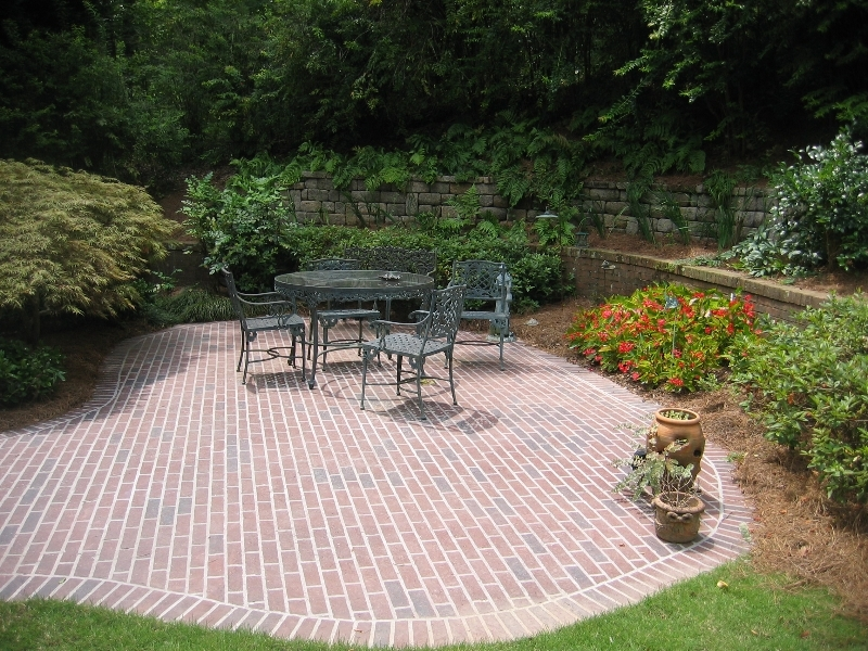 Brick patio with table and chairs next to bushes and retaining wall