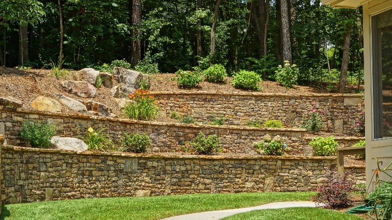 three layers of residential retaining walls with bushes