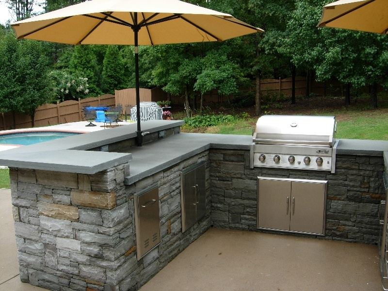 Outdoor kitchen with grill and umbrellas on pool deck