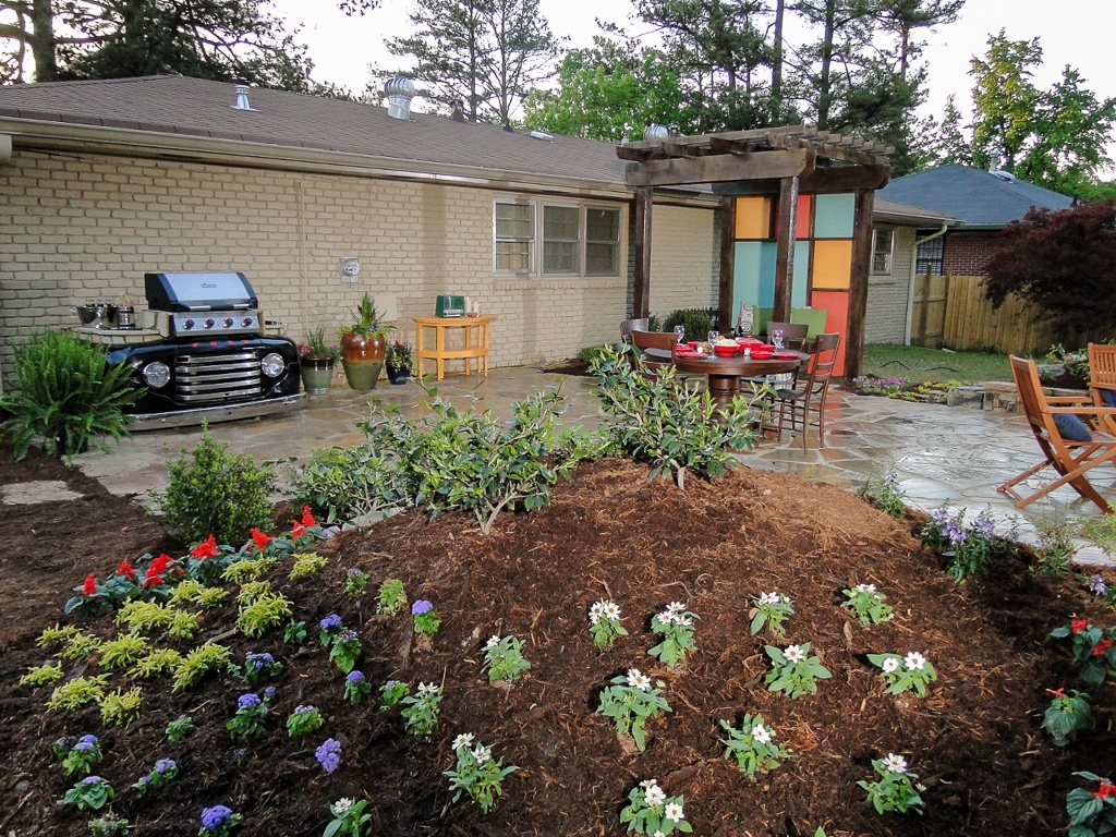 Themed patio and outdoor kitchen with flower bed