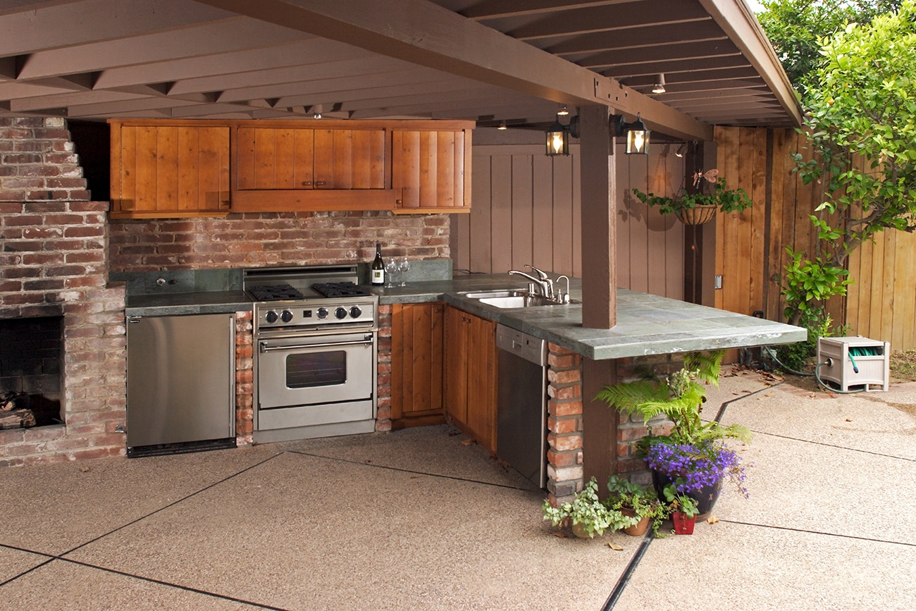 outdoor kitchen with appliances and fireplace